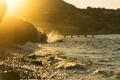 Stony beach with waves. Stony beach with waves and with golden colored sun lights in the evening stock photos
