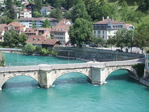 Stony bridge over clean alpine Aare river in city of Bern. BERN BERNE, SWITZERLAND, bridge over clean alpine Aare river with clean water and cityscape landscape Royalty Free Stock Photo