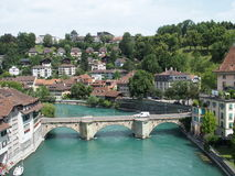 Stony bridge over clean alpine Aare river in city of Bern. BERN BERNE, SWITZERLAND, bridge over clean alpine Aare river with clean water and cityscape landscape Royalty Free Stock Photos