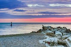 Stony coastline at sunrise. Stony coastline with a cloudy  sunrise Royalty Free Stock Images