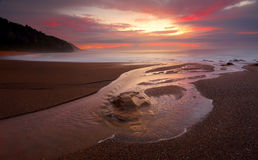 Stony Creek meets the ocean at sunrise. Long exposure at dawn as Stony Creek flows into the ocean, its waters capturing the light and colour of sunrise which Royalty Free Stock Photo