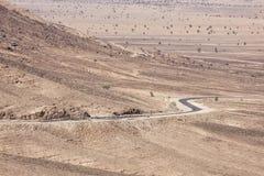 Stony desert landscapes with road and acacia trees. Stock Photos