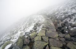 Stony Footpath in Winter Landscape Leading Into Fog Royalty Free Stock Photography