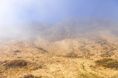 Stony hill in a fog on the shore of the fjord in eastern Iceland Stock Photos