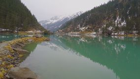 Stony lakeside, forest and mountains reflection in water, electric power lines. Stock footage stock video