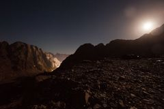 Mountains at night, lit with moonlight against sky background. Stock Image