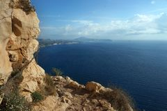 A stony path at the edge of the mountain, below is a blue sea.  stock photos