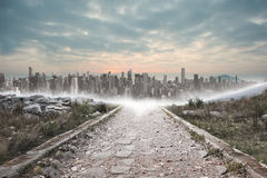 Stony path leading to city on the horizon Royalty Free Stock Images