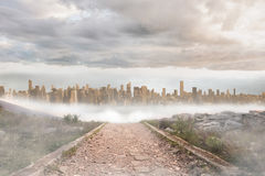Stony path leading to large urban sprawl. Under cloudy sky Royalty Free Stock Photography