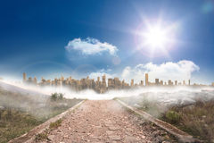 Stony path leading to large urban sprawl. Under the sun Stock Photos
