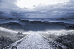 Stony path leading to mountains. Stony path leading to large misty mountains Stock Image