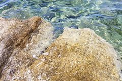 Stony shore and clear water of the Aegean Sea. Stock Photo