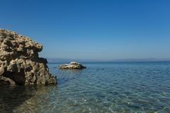 Stony shore on idyllic seascape. Rock in sea water on sunny blue sky. Wild nature, environment and ecology. Holiday Stock Images