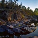 Stony shore of Ladoga lake at sunset Royalty Free Stock Image