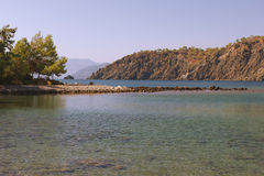 Stony spit, Mediterranean Sea, and mountains. Royalty Free Stock Image
