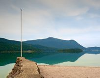 Stony sporty port at mountain lake. End of wharf with empty pole without flag. Dark blue clouds Stock Photography