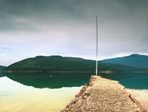 Stony sporty port at mountain lake. End of wharf with empty pole without flag. Dark blue clouds Stock Image