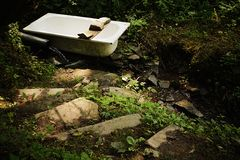 Stony stairs leading to old bathtub and rubber pipe in small forest stream Stock Images