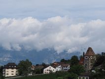 Tower and scenic housing estate on hill at cityscape landscape of clouds above european capital Vaduz city Liechtenstein. Stony tower and scenic housing estate royalty free stock image