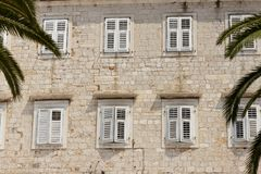 Stony wall and white windows Stock Photo