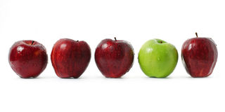 Stood Out. A green apple being stood out among red apples isolated on white background Stock Images