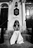 Stood Up Bride. Black and white portrait of a disappointed bride sitting on church steps with her chin in her hands, waiting for a groom who did not show for Royalty Free Stock Photos