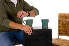 Stood up for coffee. Casual male checking his watch at coffee shop against white background, with one empty seat,  could have been stood up Stock Image