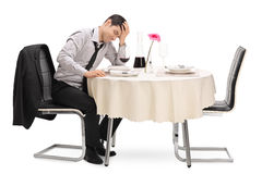 Stood up guy sitting at a table. Stood up guy sitting on a restaurant table and waiting for his date isolated on white background Royalty Free Stock Image