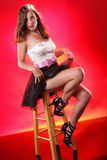 Stool diva. Pretty girl on a stool on  red background Royalty Free Stock Photos