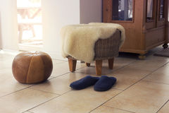 Stool with fleece and slippers in living room. By window Stock Images