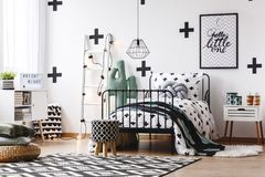 Teenager`s bedroom with cactus motif. Stool on geometric carpet and green blanket on bed in teenager`s bedroom with cactus motif stock image