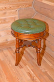 The stool with a leather upholstery stands near a timbered wall Stock Image