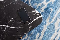 A stool made of artificial stone stands on a carpet with fine nap, a top view. The mobile phone lies on a new stool. Composition, texture, color stock photo