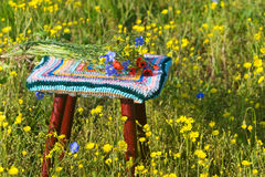 Stool with striped cover crochet and a bouquet of wild flowers Royalty Free Stock Photos