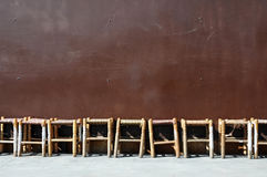 Stools. Row of wooden stools in front of a hoarding Stock Photo