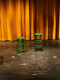 Stools on stage. Green stools on stage with a gold curtain Stock Images