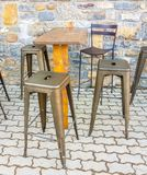 Stools and a wooden table on the outside of a bar prepared to sit for a drink. Seat furniture chair bench chrome shape business elegant model decor tall stock images