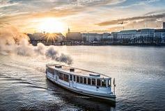 Stoomboot op Alster-Meer in Hamburg met cityscape op achtergrond tijdens zonsondergang Royalty-vrije Stock Foto