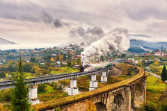 Stoomtrein die over oud spoorwegviaduct overgaan stock fotografie