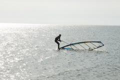 Stooping Surfer. Surfer sets the sail at sea Stock Photo