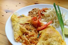 Stootkussen Thaise of Thaise die Stijl Fried Noodle Wrapped in Fried Egg Topped met Garnalen op Houten Lijst wordt gediend royalty-vrije stock foto's