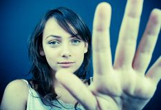 Stop. Teenager against a seamless background holds hand in front of camera Stock Image