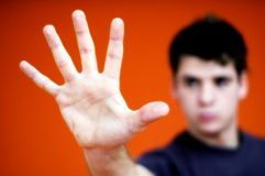 Stop!. Teenage boy holding his hand out in a stopping motion.  Hand is the focus, and closest to camera.  Teen's face is in the background, out of focus Royalty Free Stock Photography