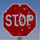 Stop. Red US STOP road sign, white lettering, blue sky background.  Sign shot through with bullet holes.  Shot (pun intended) at Monument Valley Navajo Tribal Royalty Free Stock Photos