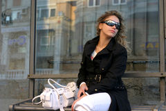 On stop. Sitting girl with sunglasses and white handbag on stop Stock Image