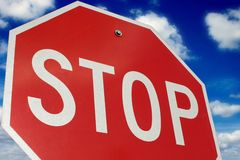 Stop!. Stop sign with clouds in background - CLOSER SHOT Stock Image