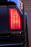 STOP. The taillight of a classic car reflects the sun to make it shine bright red as if to say STOP Stock Images