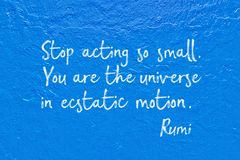 Ecstatic motion Rumi. Stop acting so small. You are the universe in ecstatic motion - ancient Persian poet and philosopher Rumi quote handwritten on blue wall Royalty Free Stock Photo