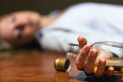 Stop alcohol!. Drunken young woman lying on the floor. Focus on the bottle Royalty Free Stock Image