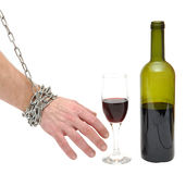 Stop alcoholism concept. Chained hand reaches for the bottle - stop alcoholism concept Royalty Free Stock Photography